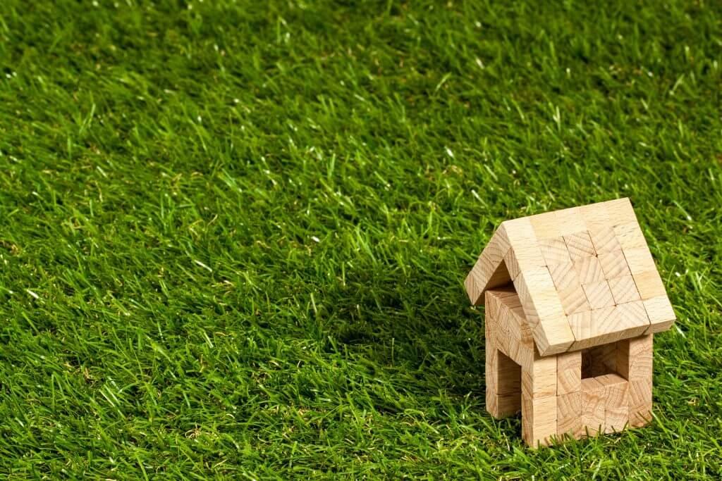 imagem de miniatura de casa de madeira representando a compra ou aluguel de imóveis.
