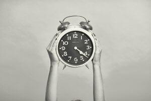 Relógio analógico sendo levantado por duas mãos femininas
