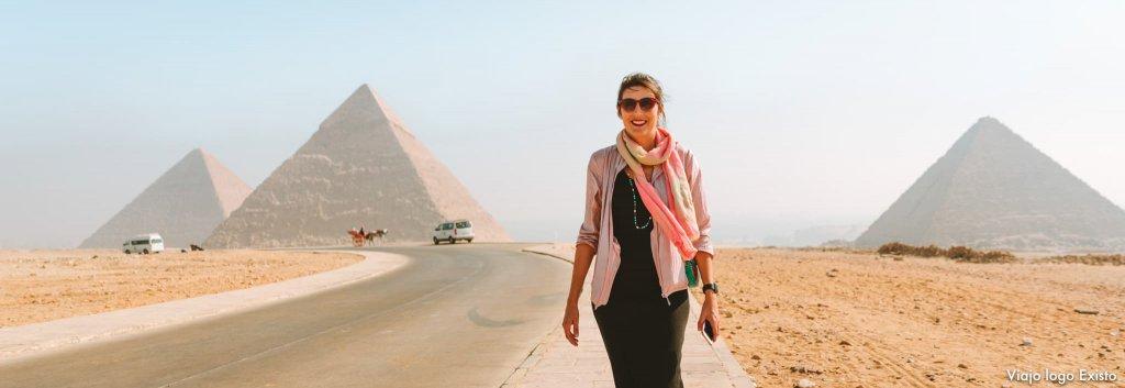 Raquel em uma estrada. Ao fundo, uma pirâmide
